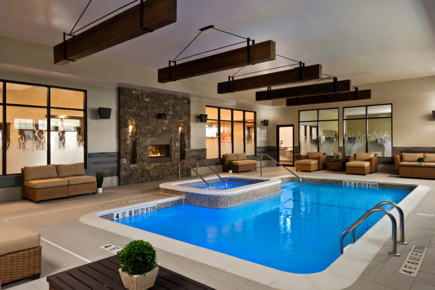 Indoor pool and hot tub with surrounding lounging area in The Lofts at Saratoga