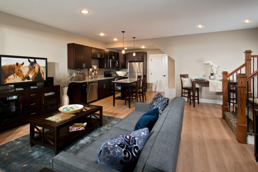 A living room and entertainment area featuring a flat screen television, coffee table, and adjoined kitchen in background.