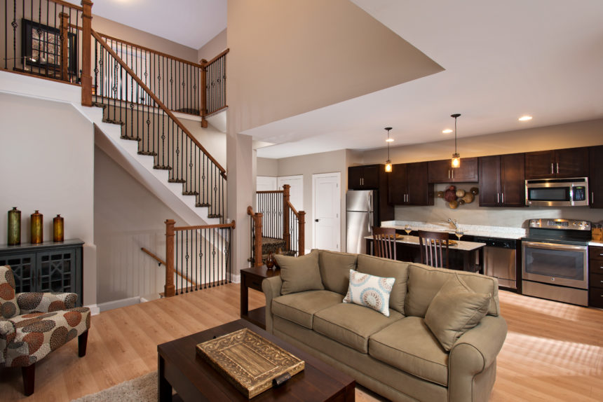 Living room at Lofts at Saratoga with hardwood floors, adjoined kitchen, and stairs in the background.