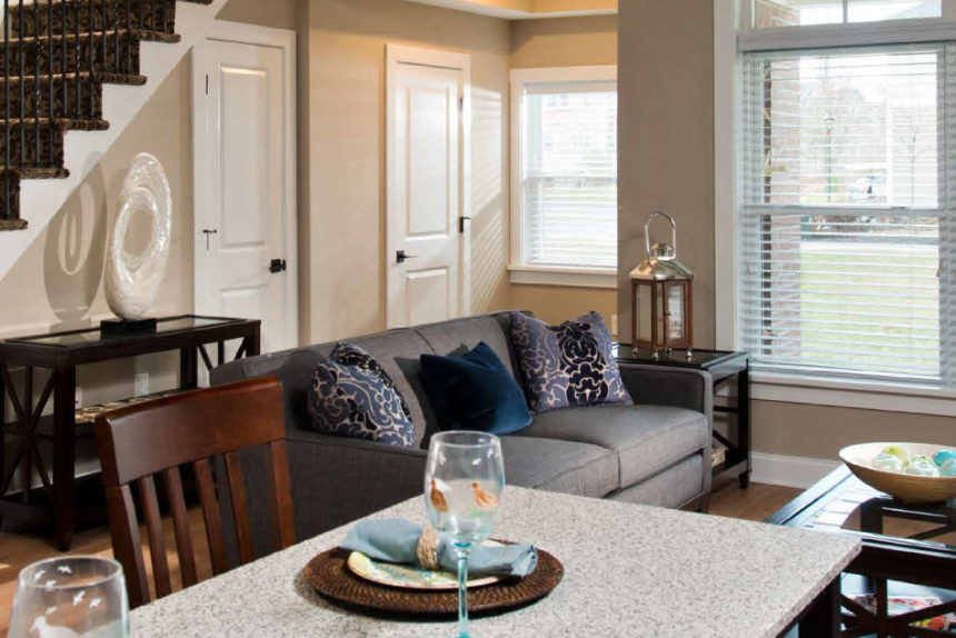 Dining room with granite countertops and wooden chairs, adjoined living room, and stairs leading to second floor.
