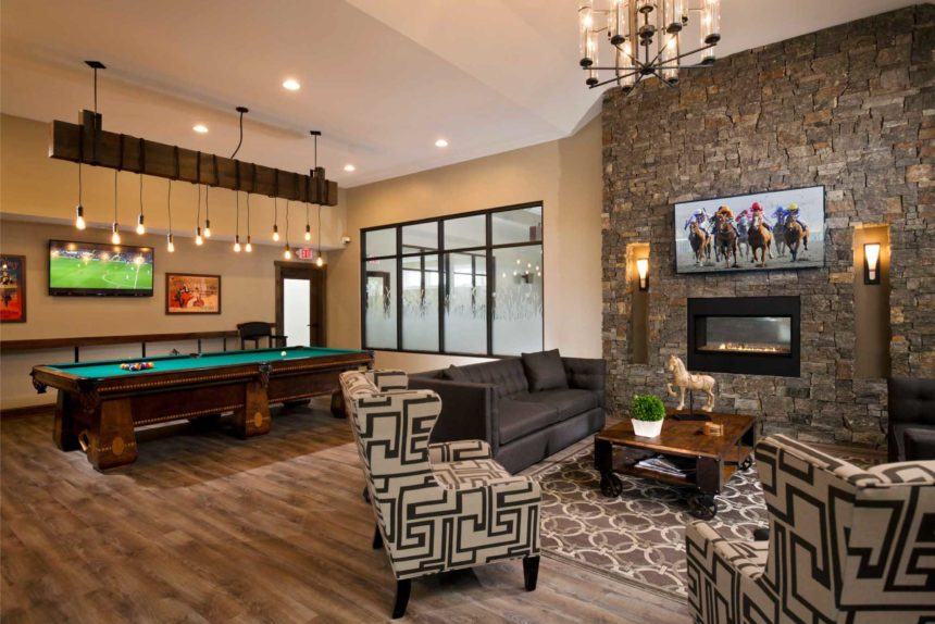 Community room at Lofts at Saratoga, featuring a pool table, a fireplace on a stone wall, television, and wooden floors.